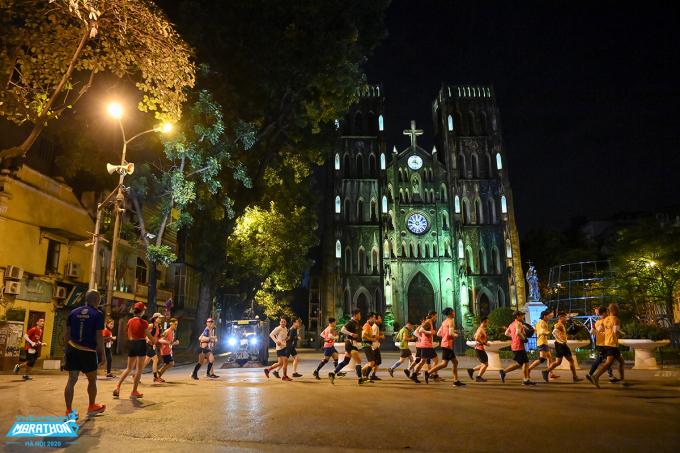 Runners run past the Hanoi Cathedral in the VM Hanoi Midnight race.  Photo: VnExpress Marathon